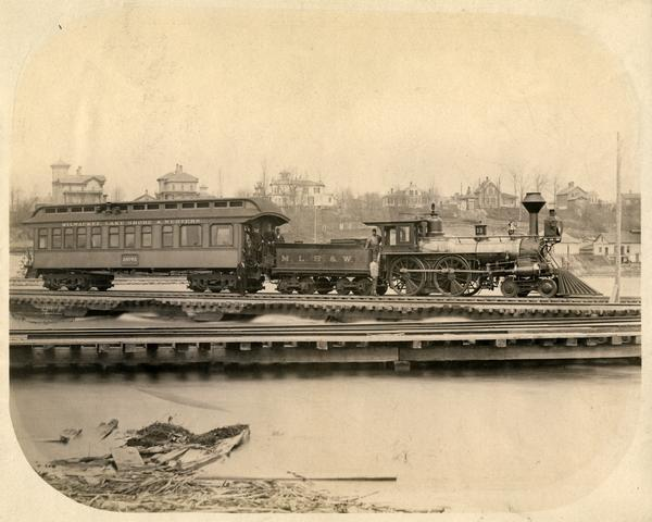 A Milwaukee, Lake Shore, and Western Railroad locomotive (No #33) pulling a pay car across a trestle over the Fox River in Appleton. Several large homes can be seen on a hill behind the train. Used by permission, Copyright Wisconsin Historical Society.